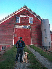 Bill Minot and his dog Turner in front of their barn built in 1802